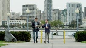 Gli uomini seri stanno discutendo l'affare mentre camminavano video d archivio