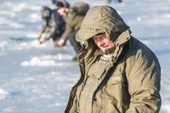 Gli uomini si siedono sul ghiaccio e sul pesce Pesca di inverno in Russia fotografie stock libere da diritti