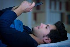 Gli uomini sociali della persona dedita di media sul letto non dormono perché Smart Phone del gioco, fondo della stanza Immagini Stock Libere da Diritti