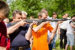 Gli uomini sparano dalle pistole pneumatiche in concorrenza Fotografia Stock