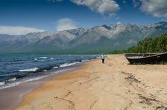 Gli uomini sta camminando in secca sulla spiaggia, vicino al lago Baikal, la Russia, un giorno soleggiato di estate fotografie stock