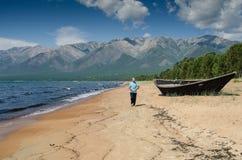 Gli uomini sta camminando in secca sulla spiaggia, vicino al lago Baikal, la Russia, un giorno soleggiato di estate fotografia stock