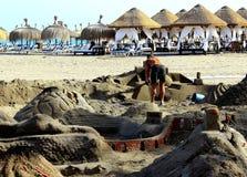 Gli uomini sta costruendo un castello enorme della sabbia sulla spiaggia Immagini Stock