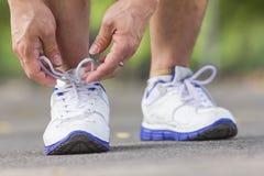 Gli uomini sta legando i pizzi di scarpe per pareggiare al parco Fotografia Stock Libera da Diritti