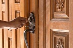 Gli uomini stanno sbloccando la porta Porta di legno della casa di legno di stile tailandese fotografie stock