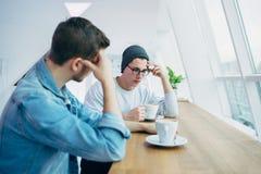 Gli uomini stanno sedendo davanti alla tavola vicino alla finestra Immagini Stock