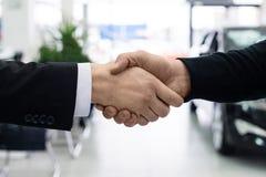 Gli uomini stringono le mani alla sala d'esposizione del commerciante di automobile fotografie stock