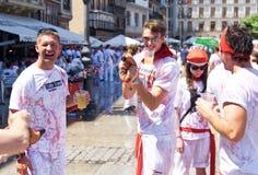 Gli uomini trasportano una latta del festival di vino di San Fermin Immagini Stock