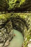 Gli uomini va su un canyon profondo nella giungla dell'Abkhazia Immagini Stock