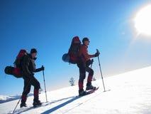 Gli uomini vanno in racchette da neve nelle montagne Immagini Stock