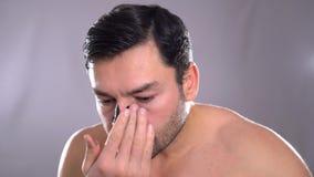 Gli usi dell'uomo pongono al giovane uomo bello crema facendo uso di crema isolata su bianco archivi video
