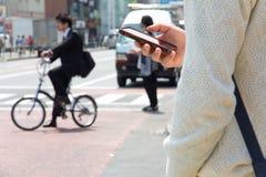 Gli usi maschii giapponesi mandano un sms alla chiacchierata sul telefono Fotografia Stock Libera da Diritti