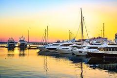 Gli yacht di lusso si sono messi in bacino in porto marittimo al tramonto variopinto Fotografie Stock