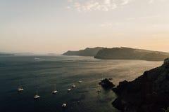 Gli yacht stanno inseguendo il tramonto su Santorini, Grecia Immagini Stock