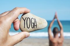 Gli Yogi equipaggiano e mandano un sms all'yoga in una pietra fotografia stock