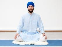Gli Yogi equipaggiano la seduta sulla stuoia immagine stock libera da diritti
