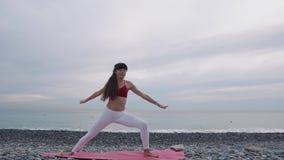 Gli Yogi femminili stanno eseguendo la posizione tradizionale del guerriero sulla riva di mare nella mattina video d archivio