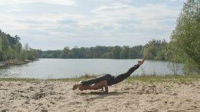 Gli Yogi tengono l'equilibrio sulle mani che stanno sulla sabbia archivi video