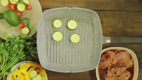 Gli zucchini verdi sono fritti in burro in una leccarda per il contorno al pollo stock footage