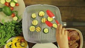 Gli zucchini verdi sono fritti in burro in una leccarda per il contorno al pollo archivi video