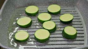 Gli zucchini verdi sono fritti in burro in una leccarda stock footage