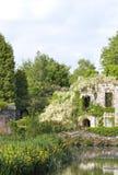 Glicínia branca em ruínas, por um lago, no jardim ajardinado Imagem de Stock