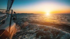 Glid seglingyachten till och med vågorna av havet under solnedgång Resor Royaltyfri Fotografi