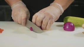 Glid ultrarapid av den yrkesmässiga kocken som hugger av grönsaker, närbild stock video
