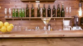 Glidare som skjutas av ett exponeringsglas av den martini drycken på en stångbakgrund lager videofilmer