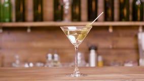 Glidare som skjutas av ett exponeringsglas av martini över en stångbakgrund lager videofilmer