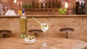 Glidaren sköt av en flaska och ett exponeringsglas av martini med oliv på en trätabell arkivfilmer