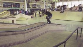 Glidbana för rullskateboradåkarebaksida på kanten av språngbrädan på konkurrens i skatepark Jippo med arg fot arkivfilmer