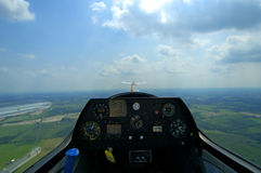 Glider Cockpit. At the controls of a glider plane while being towed by a piper pawnee. Selective focus on tow plane in front and not control panel. Blur on Stock Photos