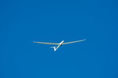 Glider in flight. A glider (sailplane) aloft, set against an azure blue sky Royalty Free Stock Image