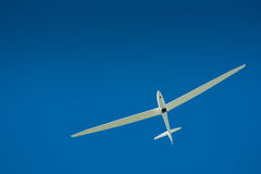 Glider in flight. A glider (sailplane) aloft, set against an azure blue sky Royalty Free Stock Photography