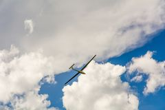 A Glider flying in bleu sky with big white clouds. The glider is a plane that has no engine Stock Photos