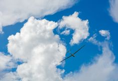 A Glider flying in bleu sky with big white clouds. The glider is a plane that has no engine Stock Photography