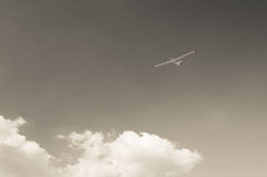 Glider. Flying in the sky above clouds. Black and white Royalty Free Stock Image