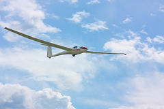 Glider flying under a blue sky. Red and white glider flying under a blue sky with white clouds Stock Photos