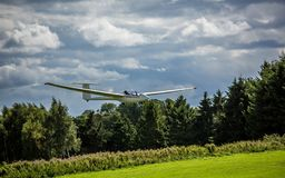 Glider land safely on the runway. After a flight around the city on a sunny and cloud summer day Stock Images