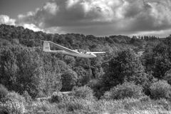 Glider landing in monochrome. K21 glider landing against a background of woody hillside Royalty Free Stock Photos