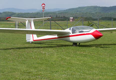 Glider. Lateral view of a glider resting on grass runway Stock Image