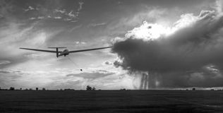 Glider Launching in Stormy Conditions. Black and white photo of glider being winch launched towards storm clouds backlit by the sun stock photo