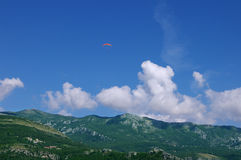 The glider pilot soars over mountains against the blue sky Stock Photos