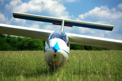 Glider plane on grass. Blue white glider plane on airpoert grass Stock Images