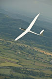 Glider, sailplane flying over countryside. Royalty Free Stock Photography