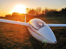 Glider at sunset. A glider is parked on the grass with the sun setting behind Stock Photo