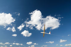 Gliders in the air. Two gliders showing synchronous turn high in the sky next to the clouds. Motion blur is used to show the speed royalty free stock images