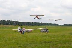 Glidflygplan som bogseras in i himlen av ljust flygplan Bil som bogserar glidflygplanet på flygfältet för startpunkten Arkivbild
