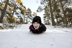 Gliding in the snow on belly. Young boy gliding on his belly in the snow Royalty Free Stock Photography